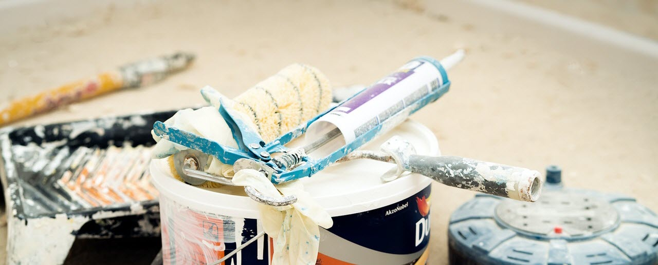 caulk gun on paint cans